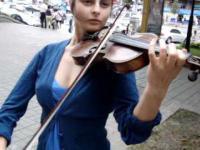 Utelantowana dziewczyna gra na skrzypcach