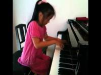 10 letnia diewczynka gra na pianinie utwór Chopina.
