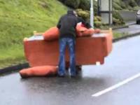 Dwóch mężczyzn transportuje kanapę