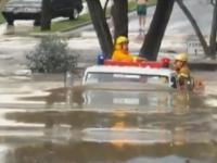 Wóz strażacki przejeżdża przez drogę zalaną przez powódź