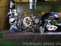 Silnik i kask motocyklowy pod prasą hydrauliczną