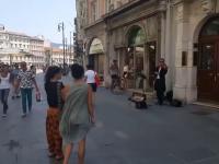 Ojciec zachęca swoją córkę aby zatańczyła do muzyki granej przez grajka ulicznego