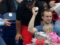Kibic łapie jedną ręką piłkę bejsbolową wybitą na trybuny
