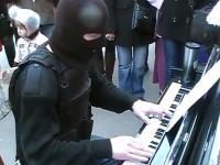 Człowiek ubrany na bojowo i w kominiarce gra na pianinie