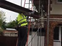 Licha drabina i nielichy robotnik wnoszący na barku duży stalowy dwuteownik