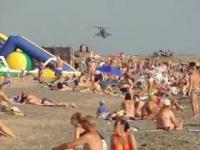Niski przelot wojskowego śmigłowca nad zatłoczoną plażą