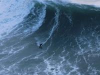 Ratownik na skuterze wodnym podejmuje surfera przed wielką falą