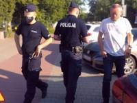 policjanci popychają pieszego na chodniku