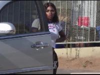 Dziewczyna pije winko podczas gdy kilku policjantów mierzy do niej z broni