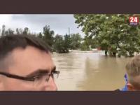 Gubernator Krymu, przeprowadza inspekcję zalanego miasta a za nim ochroniarze.